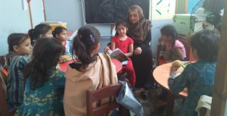 Our youngest Trustee Hafsa Sheikh reading a story to class KG 1 students.