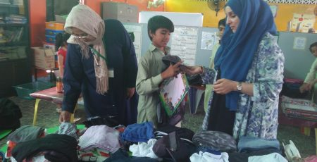Trustee Saba Haroon Sheikh distributing clothes and other gifts to students.